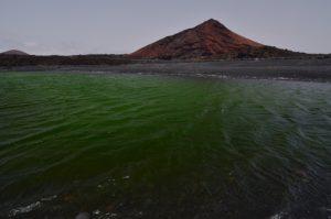 Lac vert et volcan rouge Montana Bermeja. Parque Natural de los Volcanes. Île de Lanzarote (Islas Canarias).
